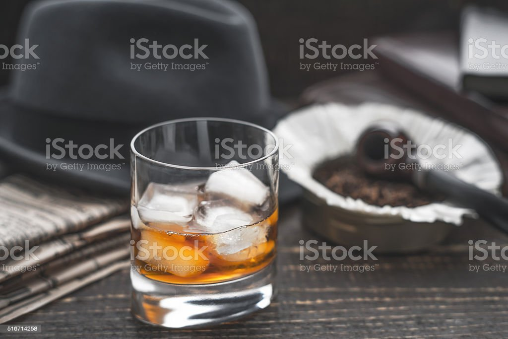 Whiskey with ice , pipe hat and newspaper horizontal stock photo