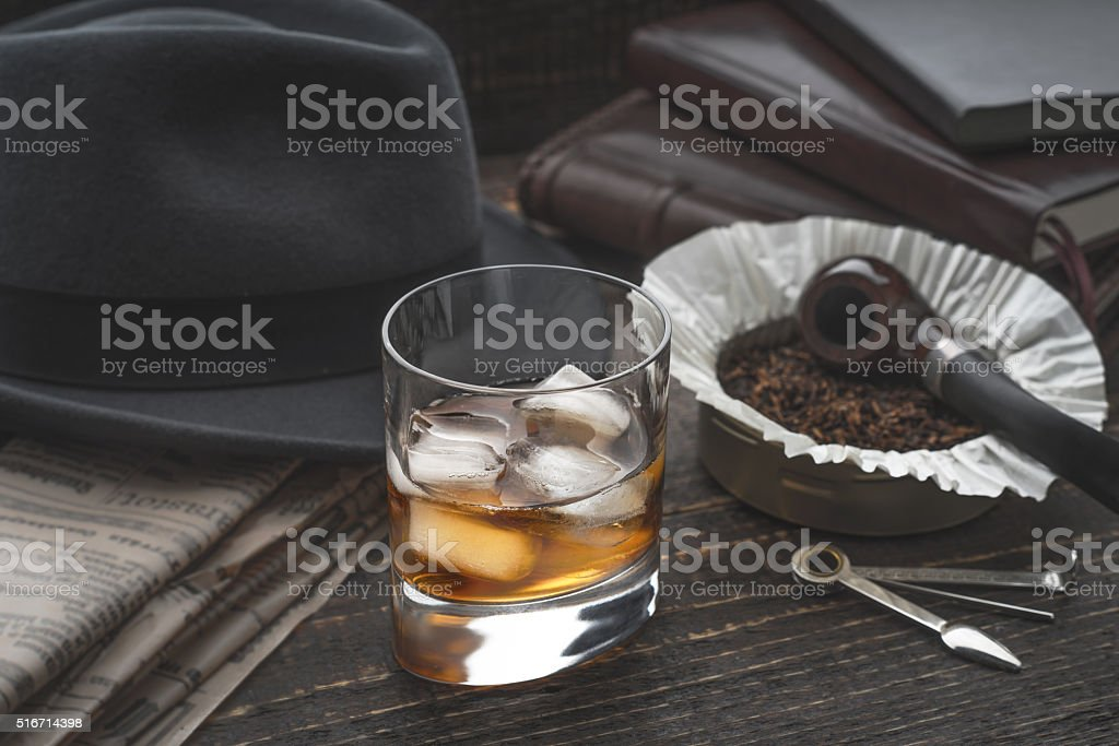 Whiskey with ice , pipe hat and newspaper stock photo