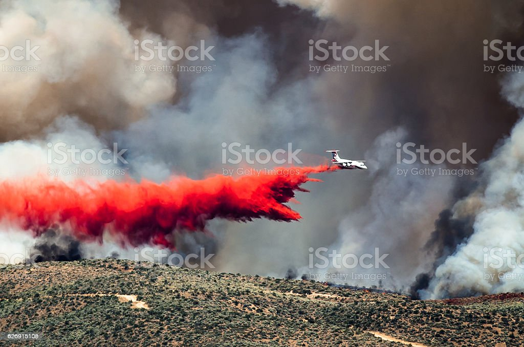 White Aircraft Dropping Fire Retardant as it Battles Raging Wildfire stock photo