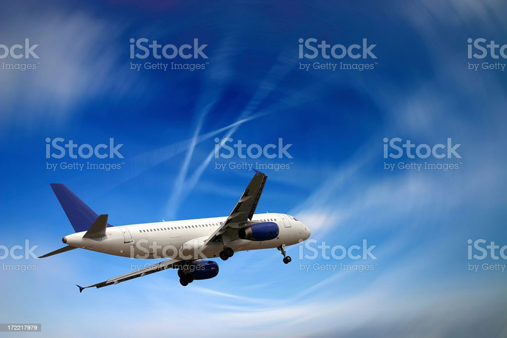 White airplane flying in a blue sky that's somewhat blurry royalty-free stock photo