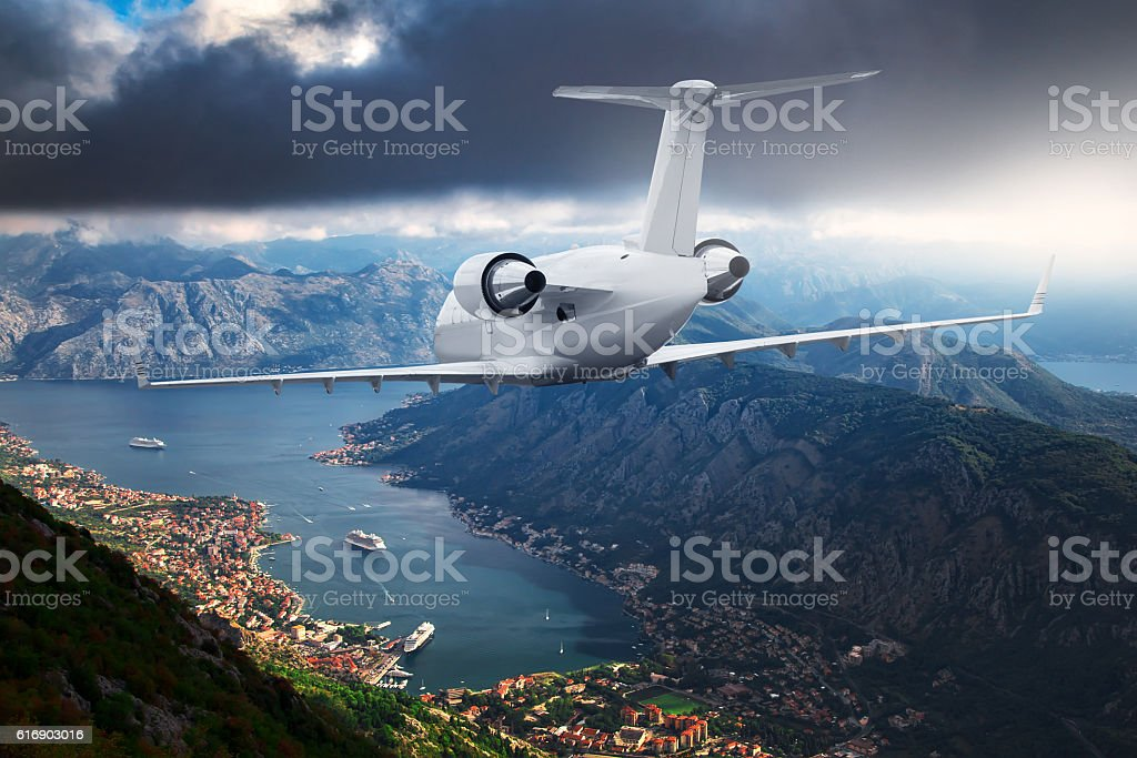 White airplane flying over sea bay resort stock photo