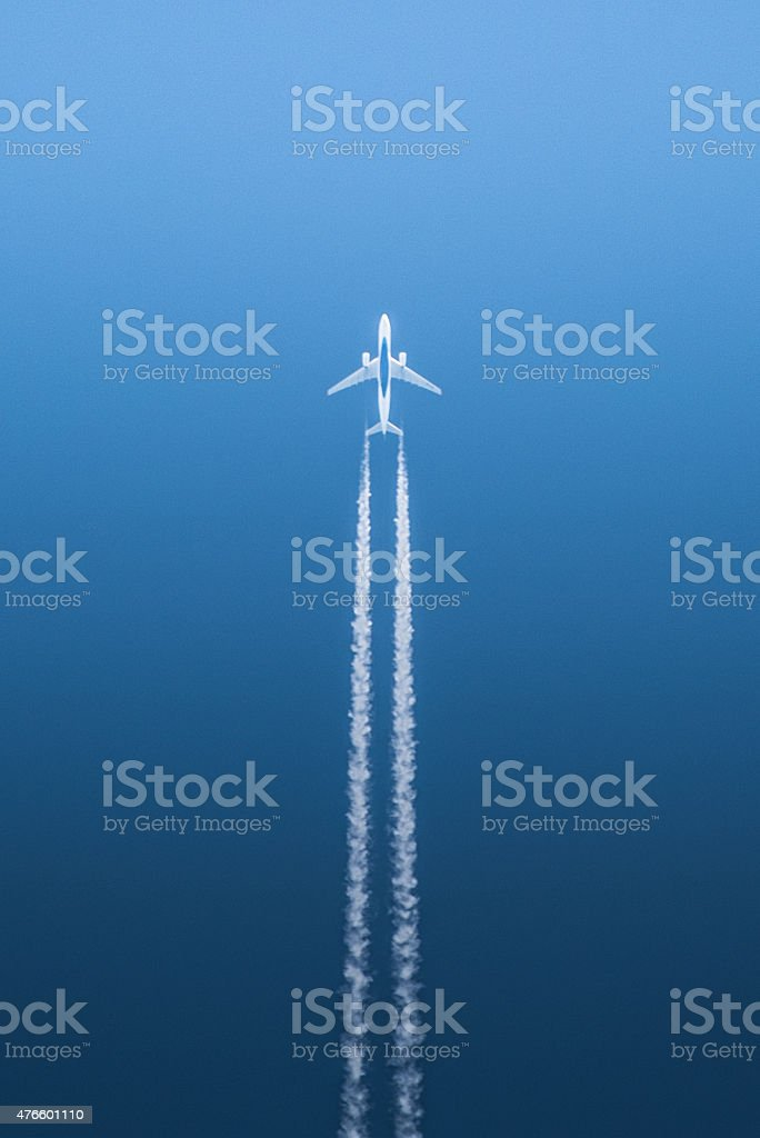 White airplane in flight against blue background stock photo