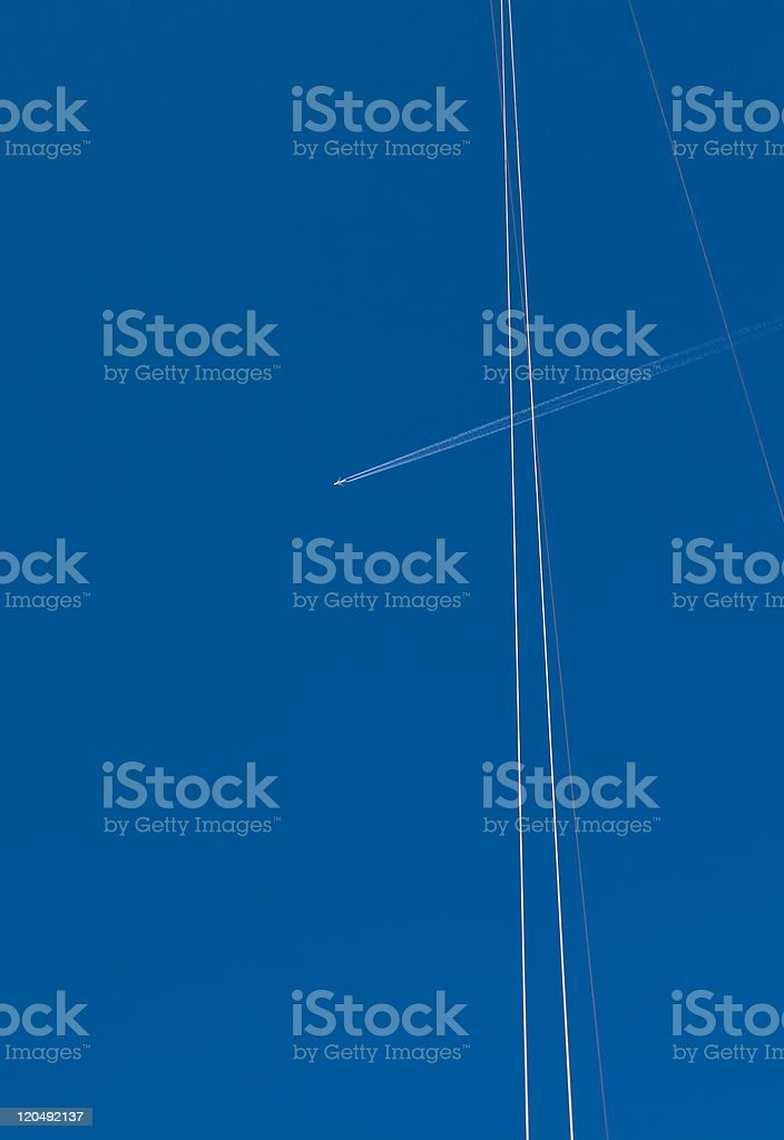 White airplane trace and wires on blue sky royalty-free stock photo