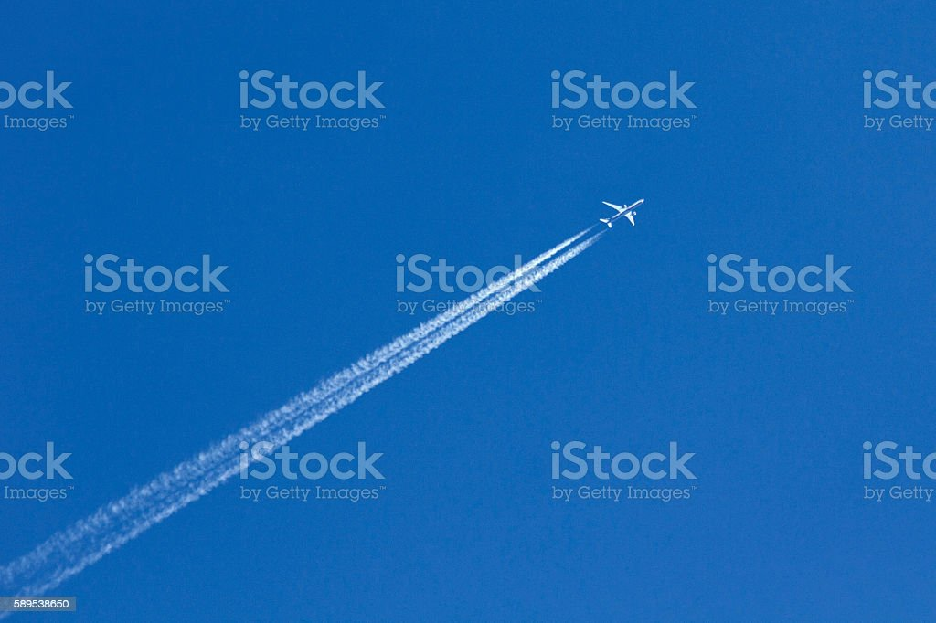 White airplane trace on blue sky stock photo