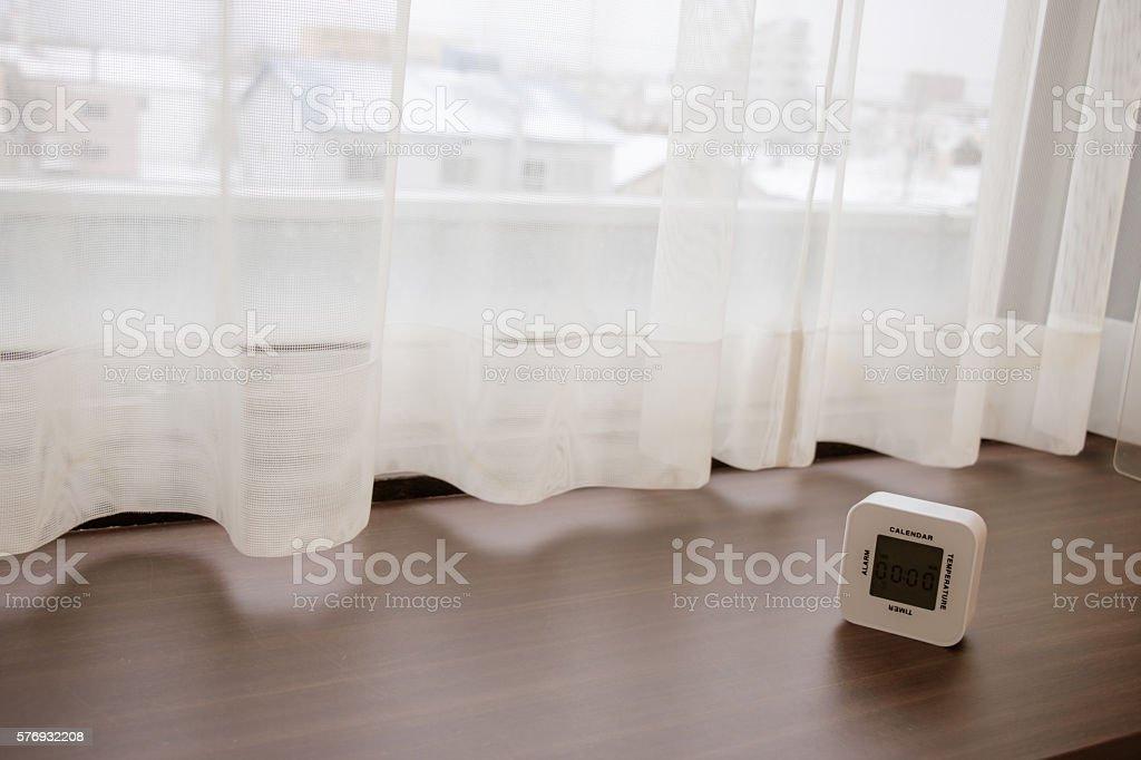 white Alarm clock on wood bar near the window stock photo
