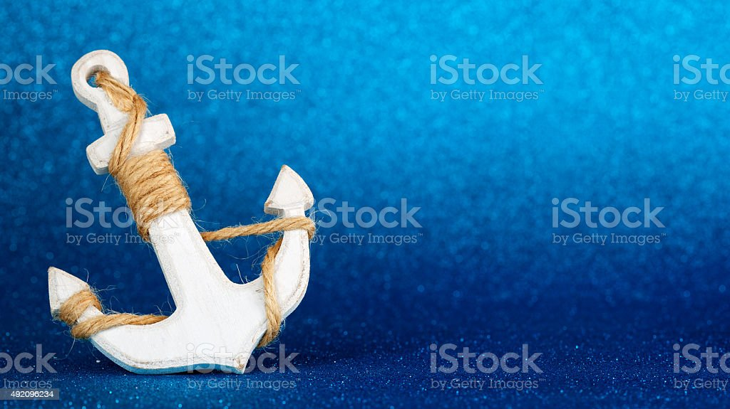 white anchor in a blue glistening backdrop stock photo