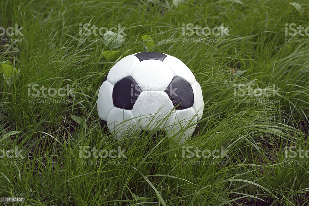 White and black ball for playing soccer in green grass royalty-free stock photo