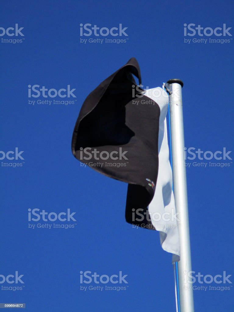 white and black flag flying a stock photo
