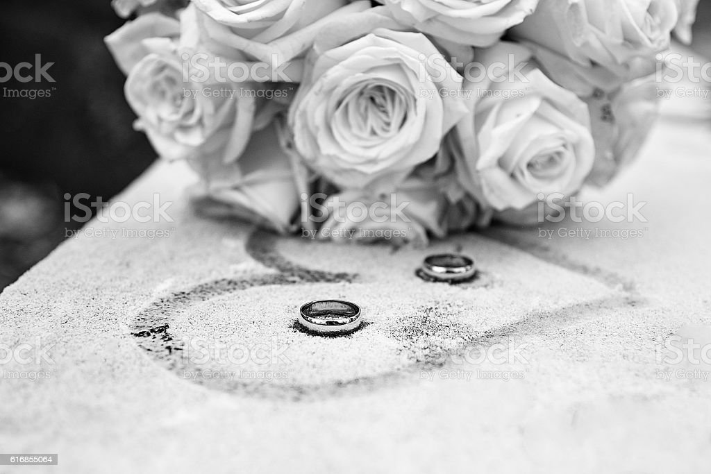 White and black flowers and rings on frozen surface stock photo