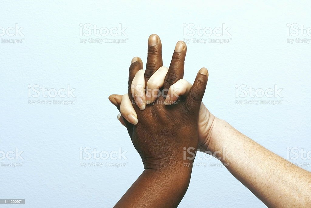 White and black hands clasped together stock photo