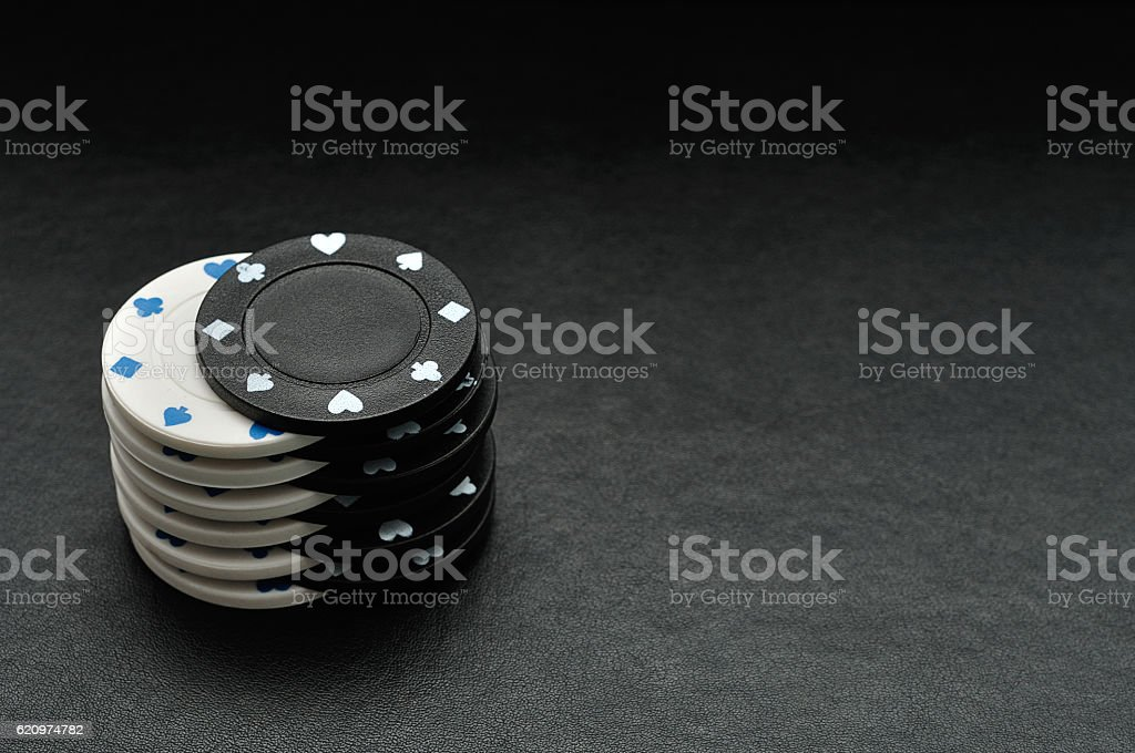 White and black poker chips on a black background stock photo
