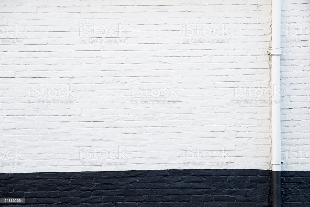 White and black wall with drain pipe stock photo