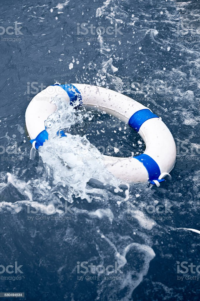 White and blue lifebelt, lifebuoy in ocean storm wave stock photo