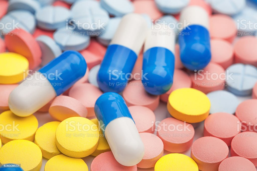 White and blue pills on background of colored medical pills stock photo