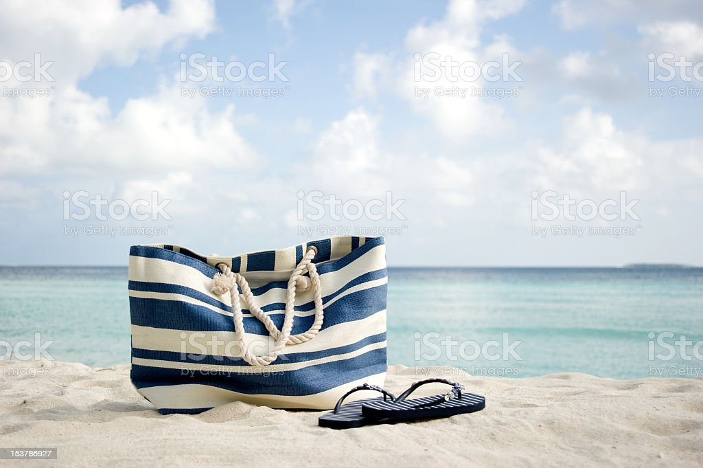 White and blue striped bag and flip-flops in beach sand  royalty-free stock photo