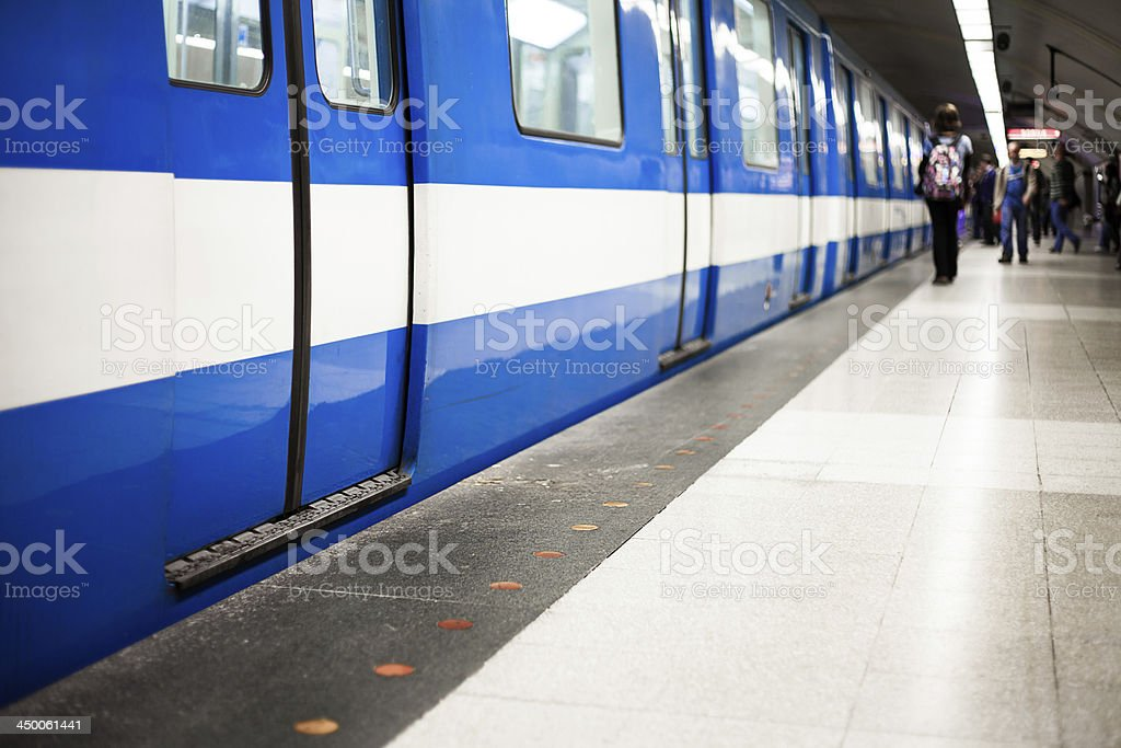 White and blue underground train in a station stock photo