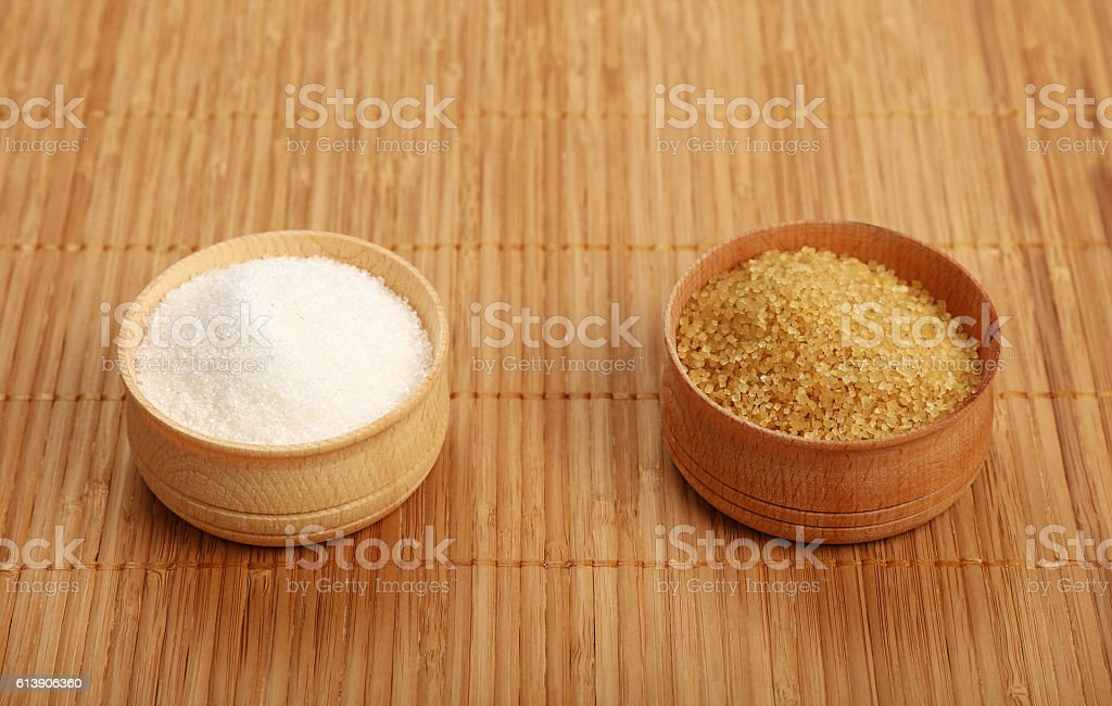 White and brown cane sugar in wooden bowls on mat stock photo