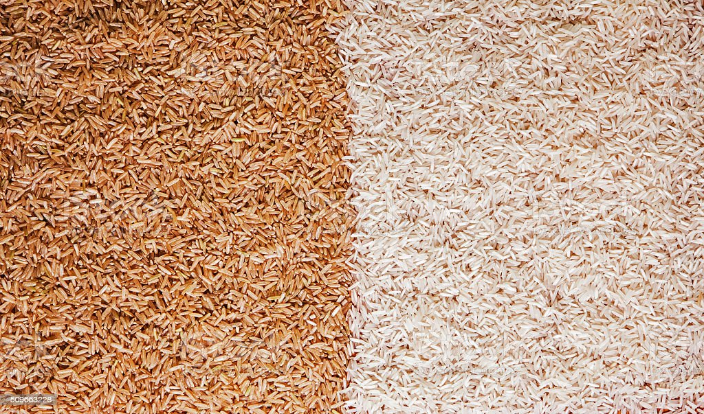 White and brown rice grains - contrast background texture. stock photo