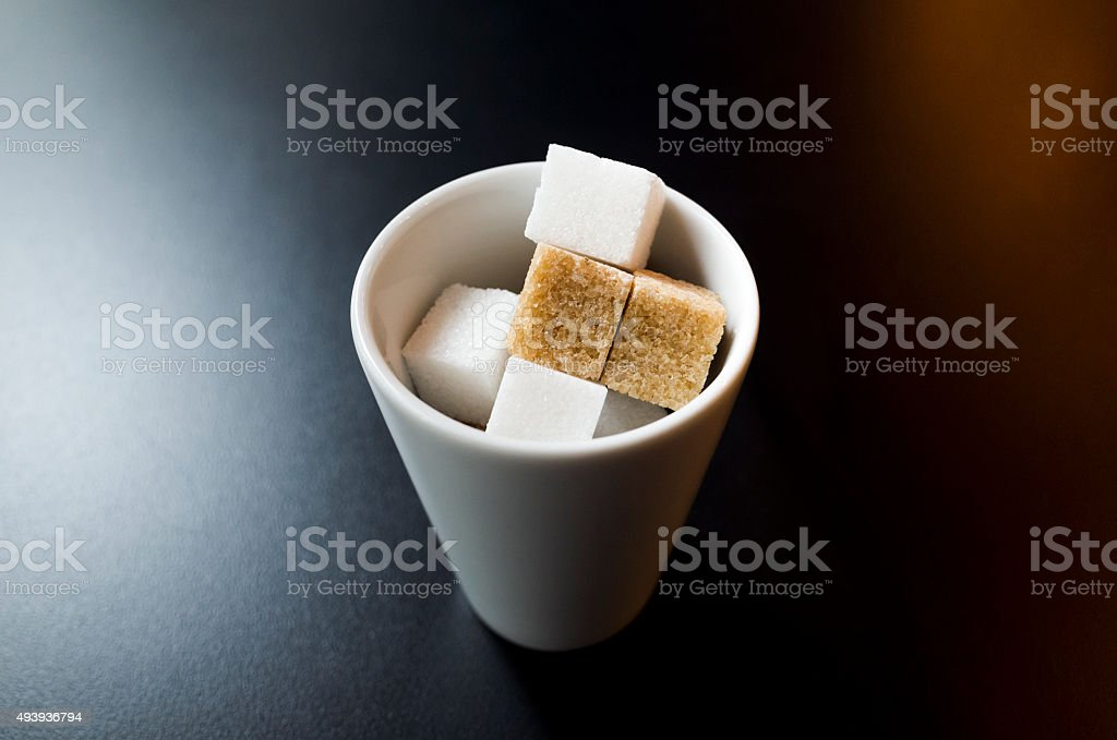 White and brown sugar cubes in round porcelain bowl stock photo
