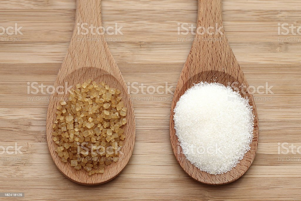 White and brown sugar in a wooden spoons royalty-free stock photo