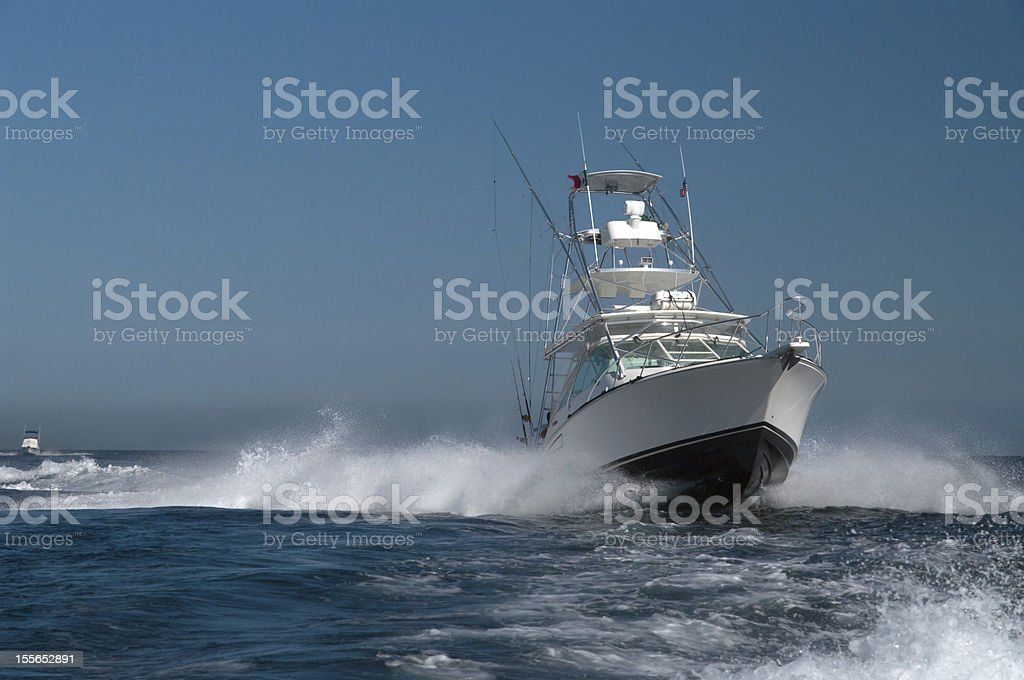 White and dark blue yacht in the ocean stock photo