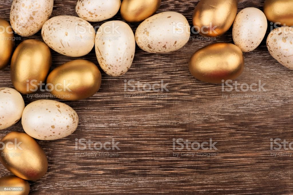 White and gold Easter egg corner border over rustic wood stock photo