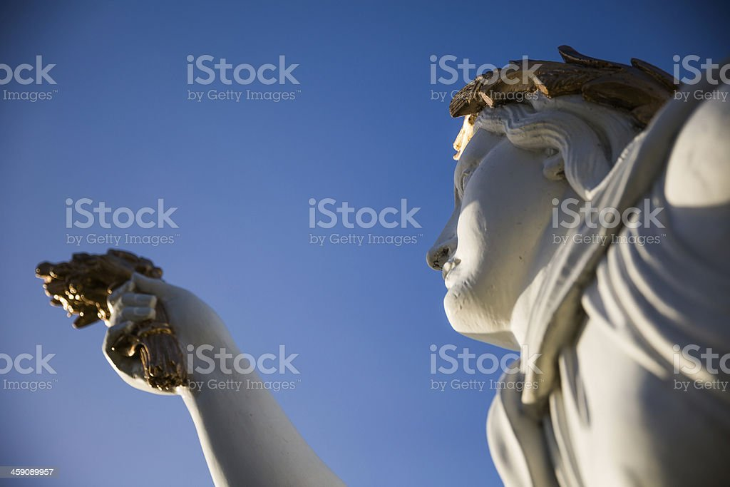 White and golden figurehead against deep blue sky stock photo