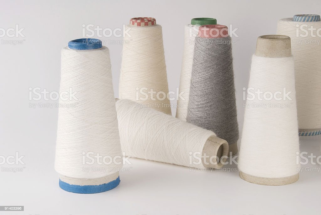 White and gray sewing thread spools, close up royalty-free stock photo
