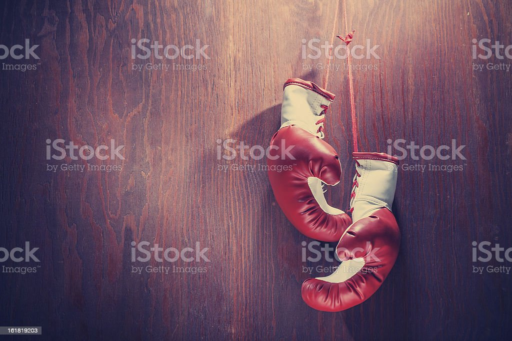 White and red boxing gloves hanging from wood background stock photo