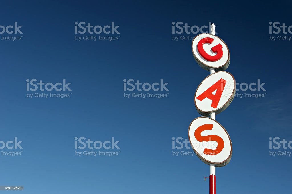 White and red retro gas sign against a blue sky background royalty-free stock photo