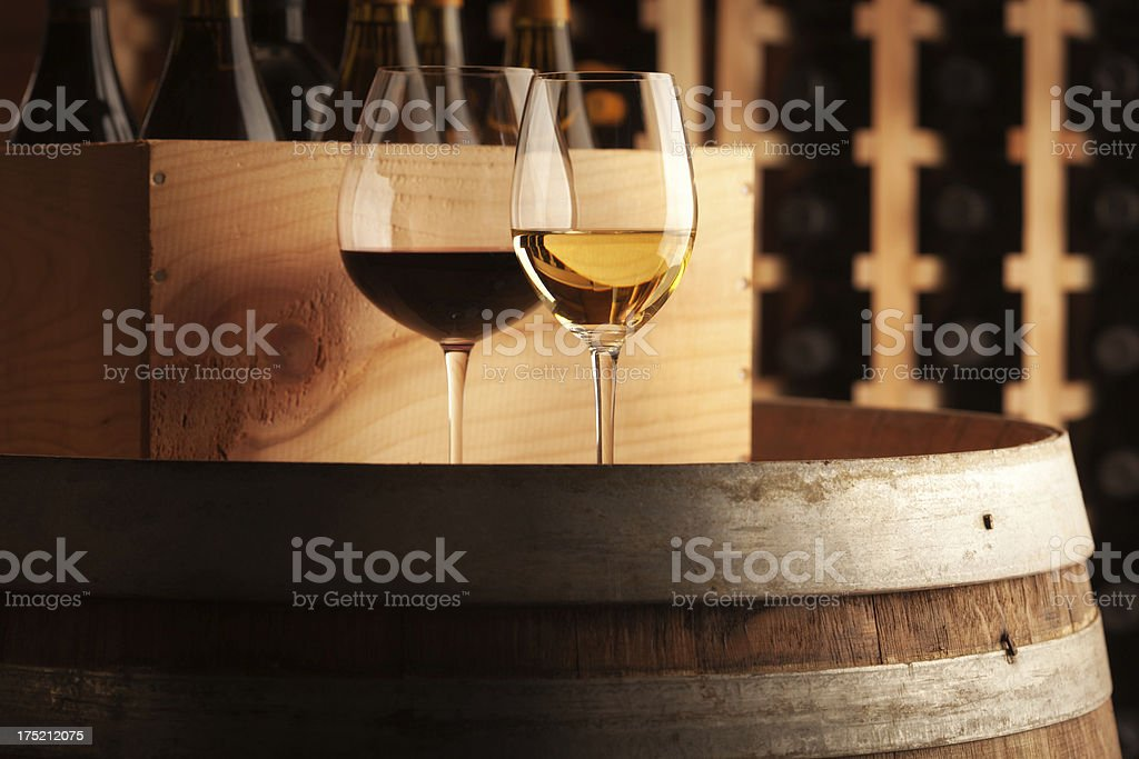 White and Red Wine Glasses on Barrel by Cellar Racks royalty-free stock photo