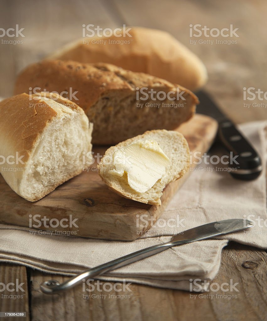 White and whole grain bread on wooden chopping board. stock photo
