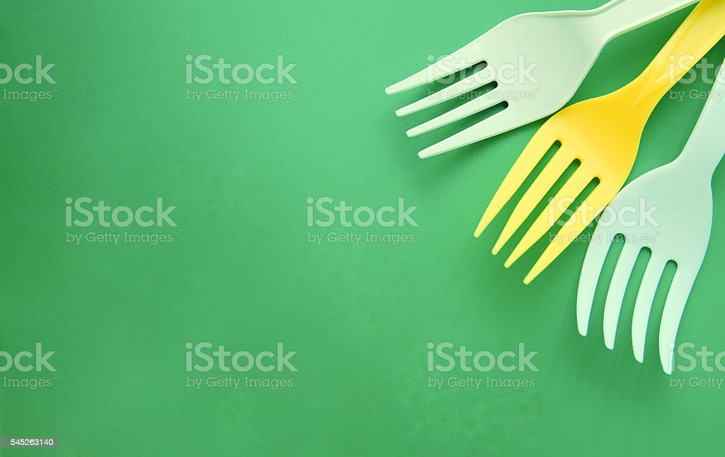White and yellow plastic forks arranged in a corner foto de stock libre de derechos