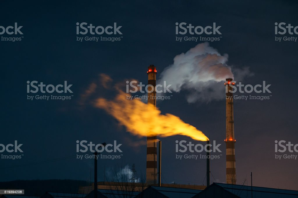 White and yellow steam from boiler at night stock photo