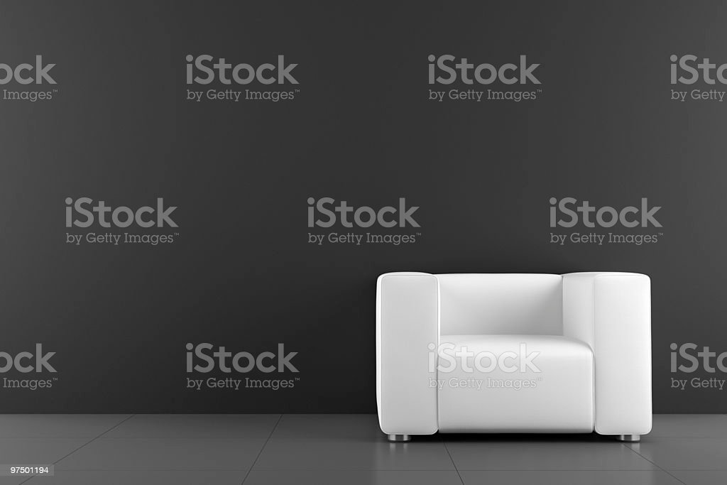 white armchair in front of black wall stock photo