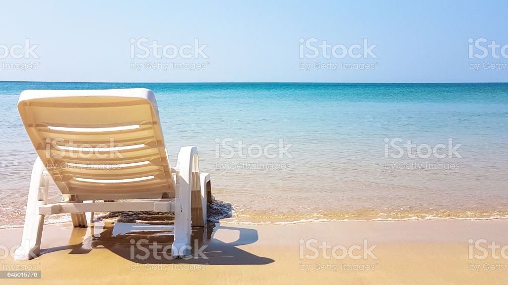 white armchair on the wet beach in sunny time stock photo