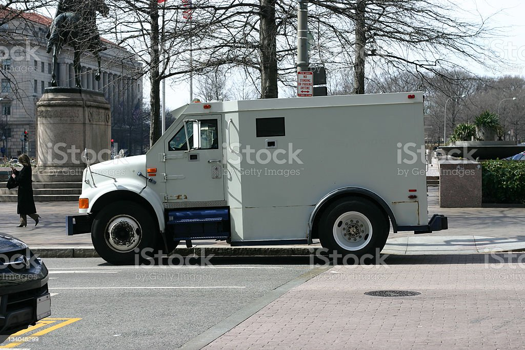 A white armored car driving through the city royalty-free stock photo