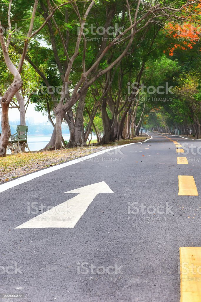 White arrow sign marking on road surface stock photo