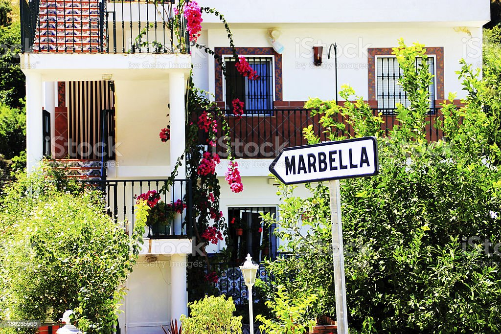 White arrow sign pointing towards Marbella in a village stock photo