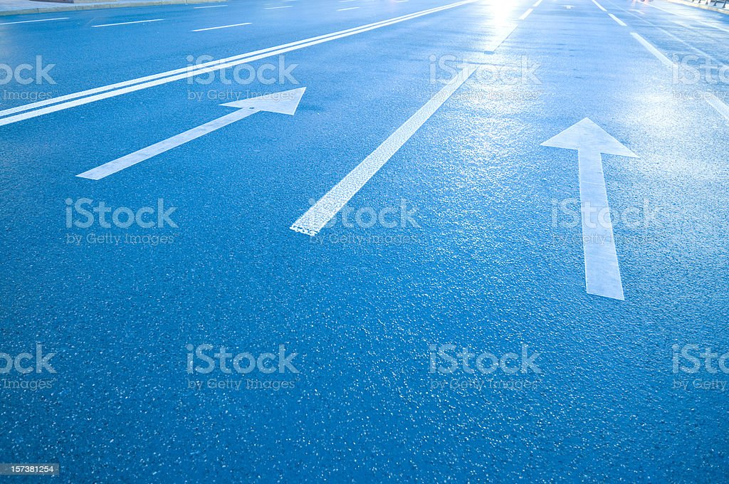 White arrows and lines on blue road royalty-free stock photo