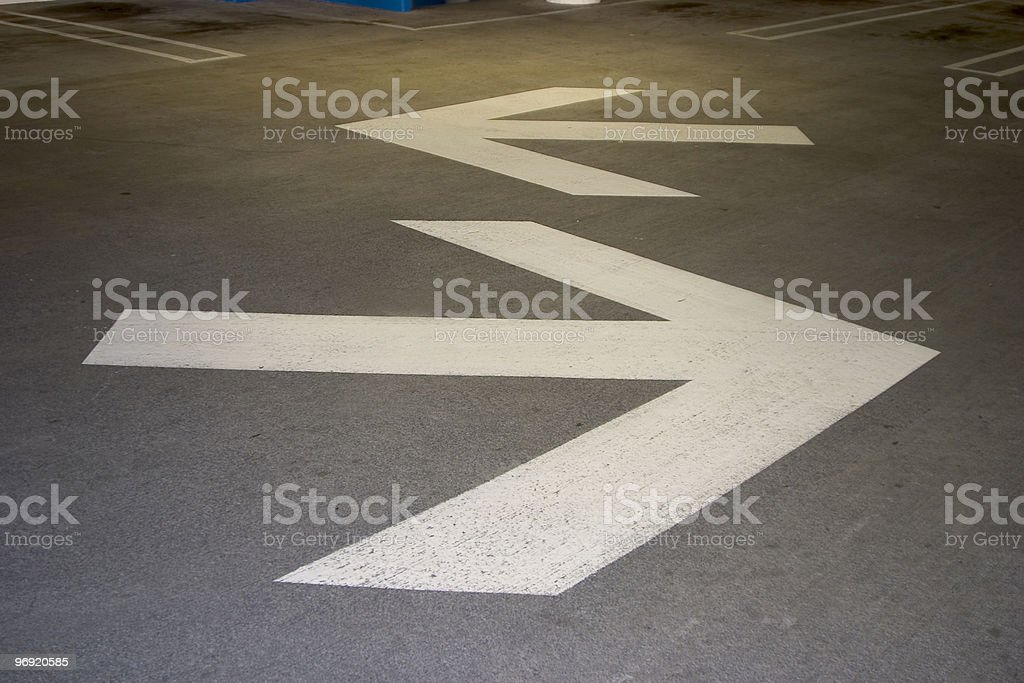 White arrows on gray asphalt parking structure stock photo