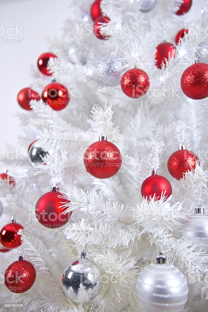 White Artificial Christmas with Red and Silver Glitter Baubles stock photo