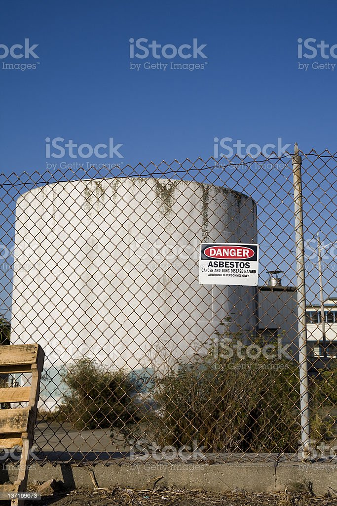 White Asbestos Warming Sign on High Chainlink Fence stock photo