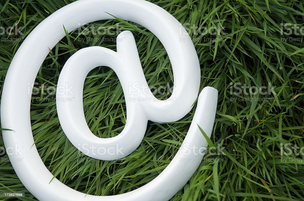 White @ At Sign Symbol Green Grass stock photo
