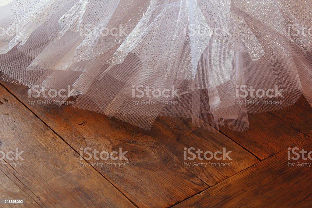 White ballet tutu on wooden floor stock photo