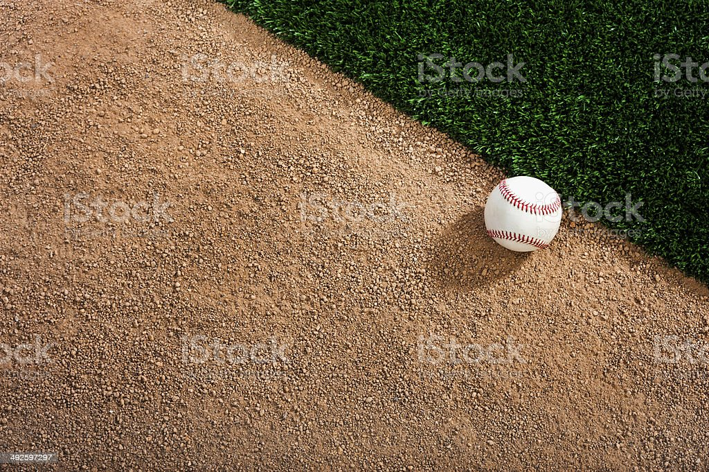 White baseball on a dirt track next to the grass stock photo