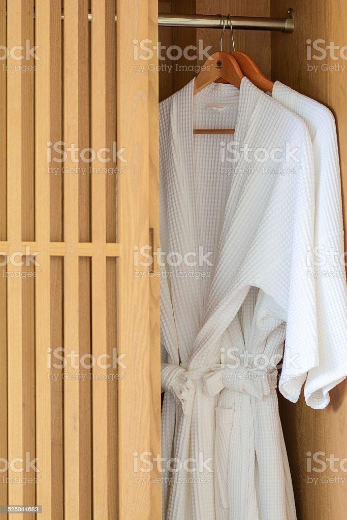 white Bathrobe in wood wardrobe stock photo
