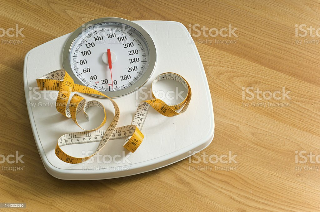 A white bathroom scale with yellow tape measure  stock photo