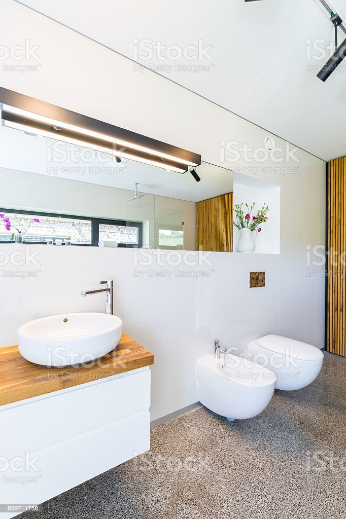 White bathroom with wooden details stock photo