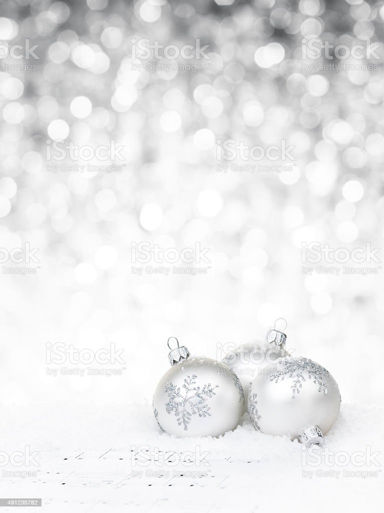 White baubles on sheet notes against defocused light background stock photo